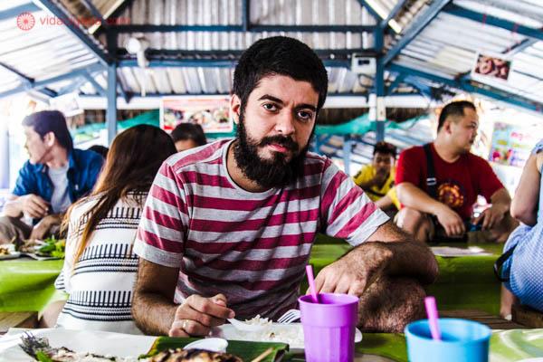 Um homem comendo no mercado tailandês