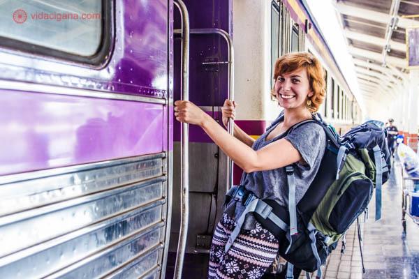 Dicas Tailândia com uma mulher subindo num trem com um mochilão nas costas