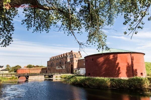 O que fazer em Malmö: o Castelo Malmohus vermelho no meio do lago, com uma ponte ligando ao outro lado