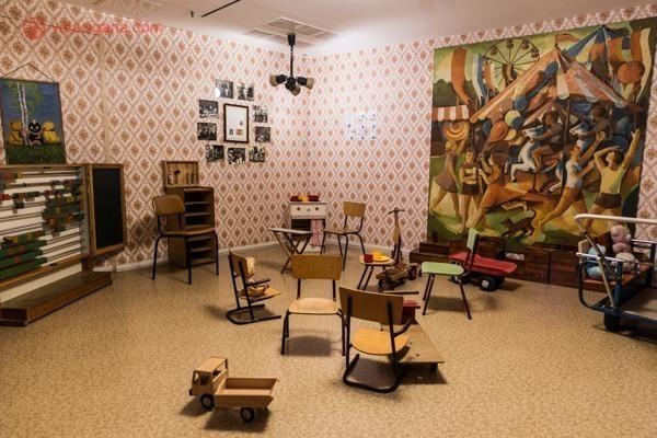 uma sala de aula da alemanha oriental, com cadeiras, posteres comunistas