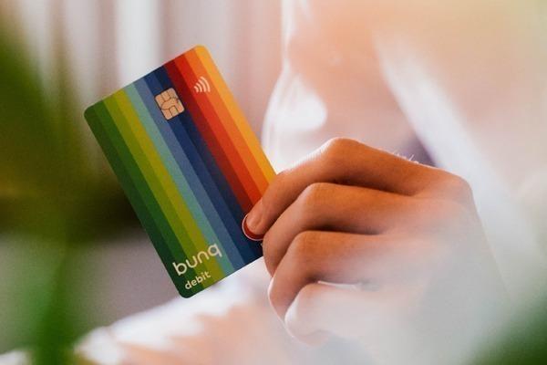 Um cartão Bunq sendo segurado por uma mão masculina