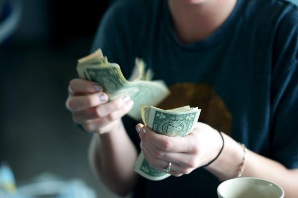 Uma mulher contando várias notas de dólares
