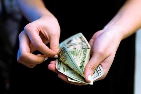 Uma mulher contando notas de dólares