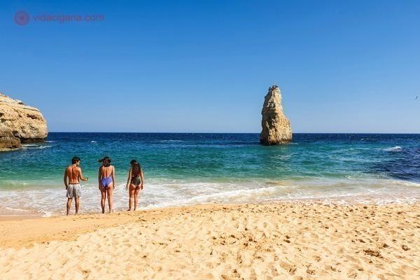 A Praia do Carvalho, com águas azuis e uma rocha no meio da água