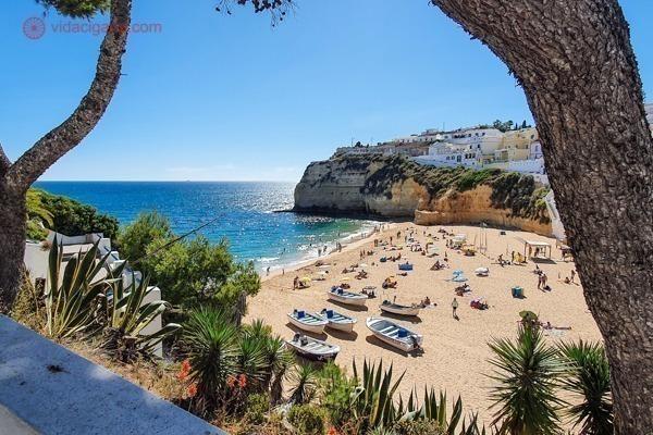 O que fazer no Algarve: a praia do carvoeiro vista da trilha, no meio das árvores, cheia de barcos de pescadores na areia