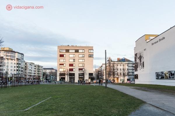 O Mauerpark, em Prenzlauer Berg, com campo verde e prédios na fronteira de onde ficava o muro de berlim