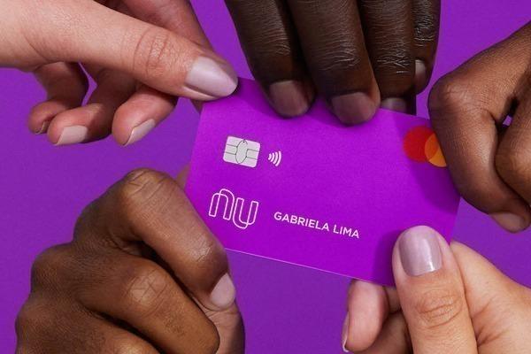 Os 7 melhores bancos digitais no Brasil: o cartão roxo do nubank sendo segurado por 5 mãos