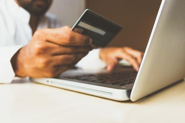 os 7 melhores bancos online no Brasil. uma mão masculina segurando um cartão e mexendo no computador