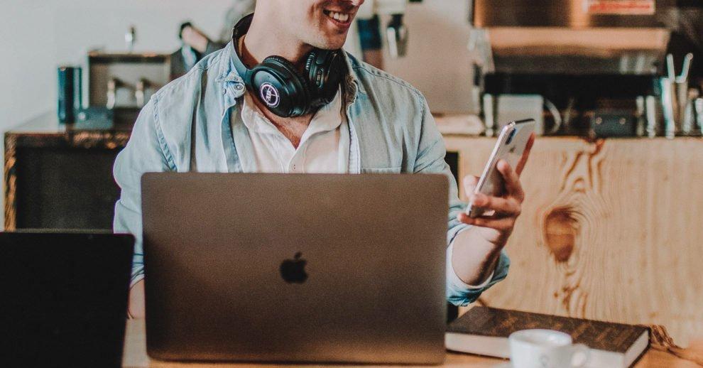 os 7 melhores bancos digitais no Brasil: um homem olhando pro celular com um laptop em frente