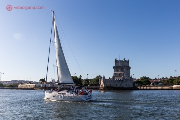 Um veleiro passando na frente da Torre de Belém