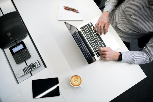 Como usar o Last Pass: um homem sentado na frente de um laptop com seu café