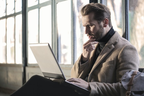 Homem olhando pra tela do computador com dúvida
