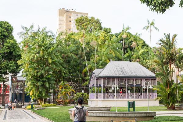 Um coreto em meio a um jardim com árvores típicas