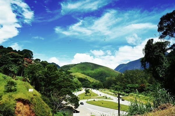 Uma rua em Itaipava cheia de verde, com colinas e céu azul