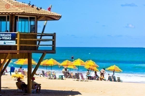 A Praia da Boa Viagem com várias barraquinhas amarelas com uma casinha de salvavidas