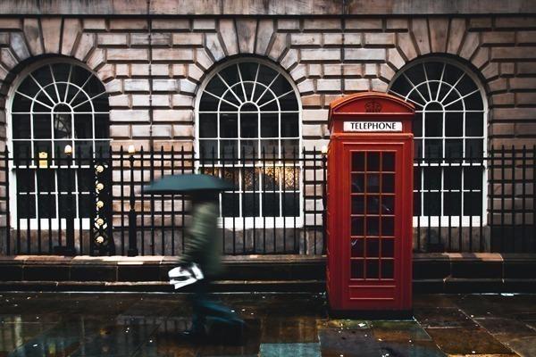 Como arrumar mala de viagem para a Europa: uma pessoa usando guarda chuva na Inglaterra