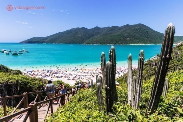 A Praia do Pontal do Atalaia, com águas cristalinas e turquesas, com sua escadaria do lado esquerdo e cactos do lado direito