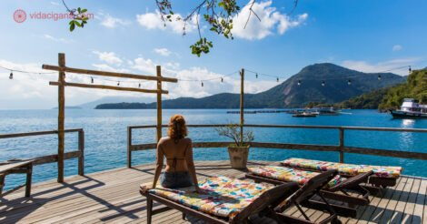 Onde ficar em Ilha Grande: uma mulher de costas sentada na beira do mar