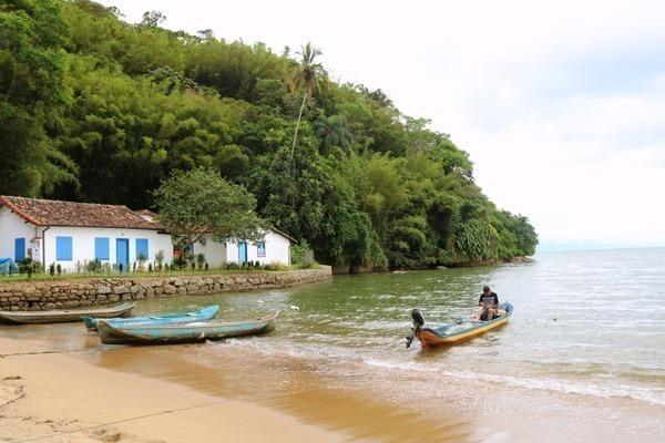 A Praia do Pontal, com 2 casas antigas na borda esquerda e um barquinho entrando no mar