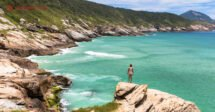 O que fazer em Arraial do Cabo: uma mulher no topo de uma pedra de frente ao mar verde
