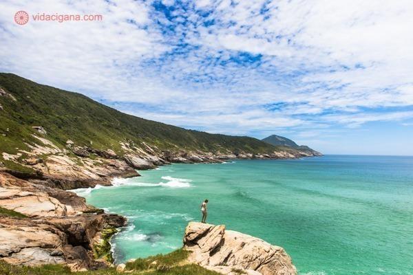 Uma mulher na borda de uma pedra na trilha para a Praia Brava, com o mar verde lá embaixo