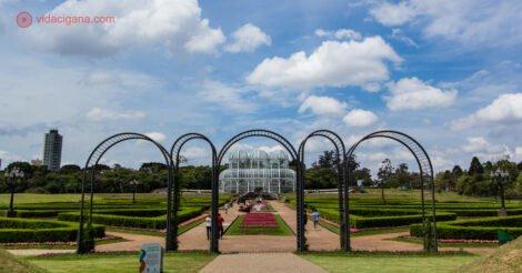 O que fazer em Curitiba: o Jardim Botânico de Curitiba, com sua cúpula no fundo, emoldurada por arcos no início do jardim