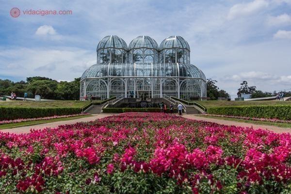 O que fazer em Curitiba: o Jardim Botânico de Curitiba com seu jardim cheio de flores vermelhas e a estufa no fundo