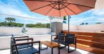 Airbnb em Curitiba: um terraço com cadeiras de sol e um guarda sol e estátua de Buda
