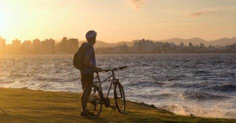 Onde ficar em Florianópolis: Um homem parado na beira do mar com uma bicicleta olhando a cidade ao fundo