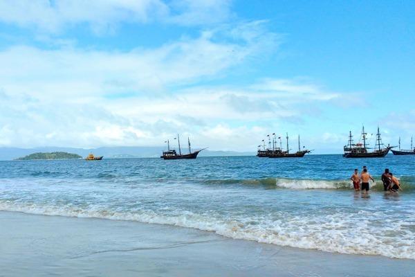 A praia de Canasvieiras num dia de céu azul com nuvens, garotos no mar e barcos no formato de caravelas ao fundo