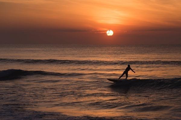 A Praia de Itamambuca durante o pôr do sol, com uma mulher surfando