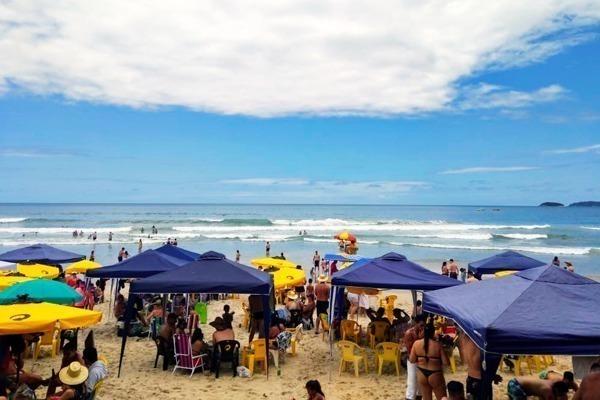 Onde ficar em Ubatuba: a Praia Grande cheia de banhistas em seus guarda sois