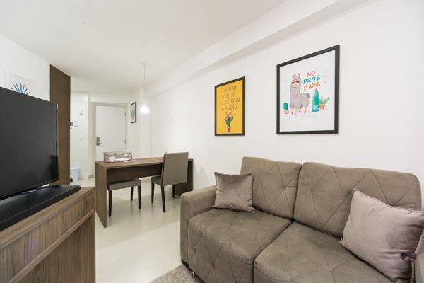 Sala bem clara neste Airbnb no Recife, com sofá marrom e TV
