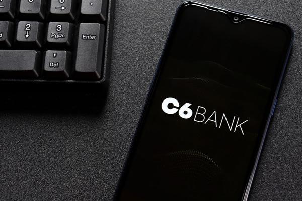 Uma tela do celular com o símbolo do C6 Bank e um teclado ao lado