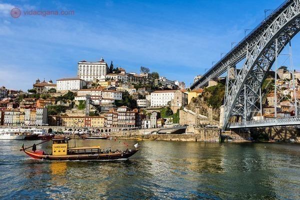 O Porto visto de Vila Nova de Gaia, na beira do Rio Douro, com a ponte D. Luis I ao lado direito e um barco rabelo navegando no rio