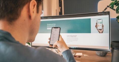 N26 vs Revolut: um homem olhando o celular na frente de uma tela de computador