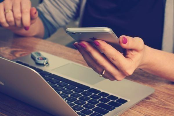 Uma mulher segurando um celular na frente de um notebook