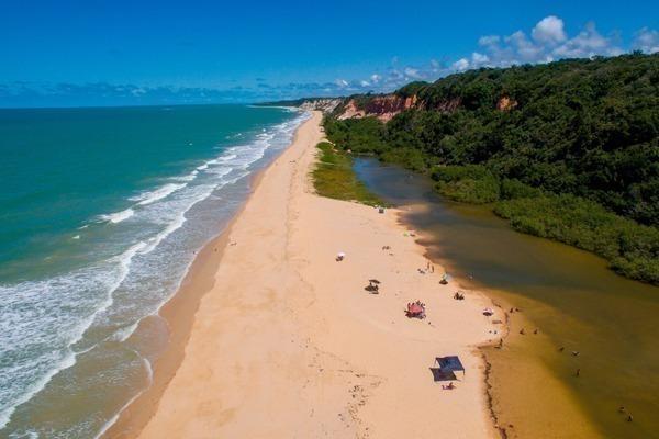 Onde ficar em Porto Seguro: uma praia selvagem imensa, com uma faixa de areia entre o mar e o rio e uma mata fechada