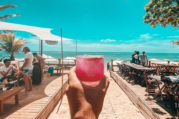 Um homem segurando um drink vermelho virado para a praia num dia ensolarado