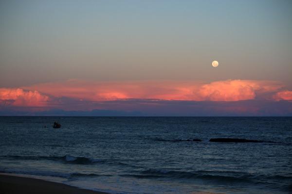 A lua cheia alta no céu com nuvens rosas e o mar
