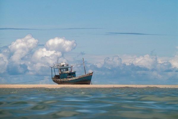 Um barco no areal em frente ao mar