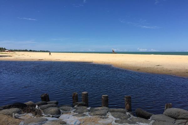 Onde ficar em Porto Seguro: a praia ao fundo com o areial no meio e um rio de cor escura em primeiro plano