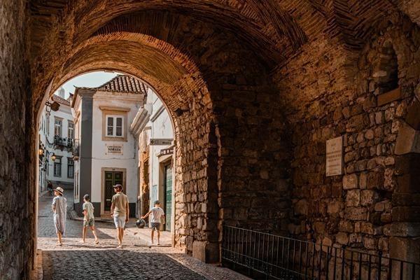 Uma família passando por um arco medieval em Faro