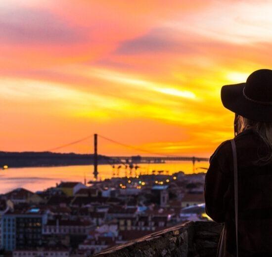 Os 9 Melhores Miradouros de Lisboa, este é o primeiro lugar, o Castelo de São Jorge, com uma mulher usando chapéu de costas vendo o rio Tejo durante o pôr do sol