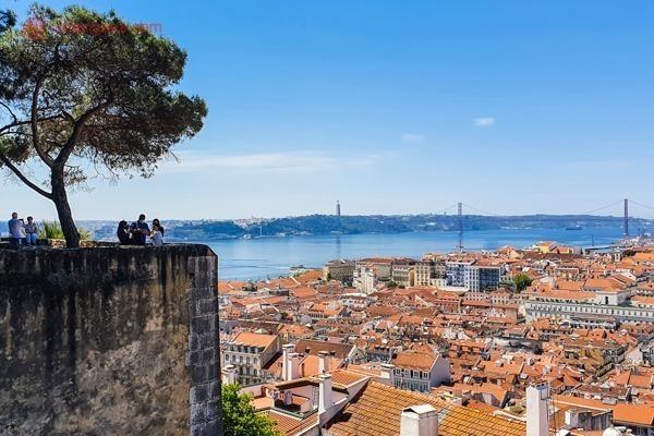 A muralha do Castelo de São Jorge com pessoas e lá ao fundo, o Rio Tejo, com o casario cor de ocre de Lisboa a frente, a Ponte 25 de Abril ao fundo