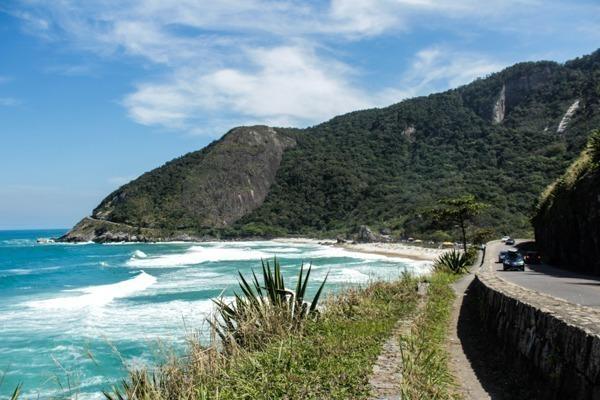 A Prainha vista da estrada que dá acesso a ela, com águas agitadas, uma montanha atrás cheia de verde e a faixa de areia na direita
