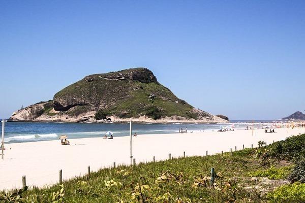 A Praia do Recreio com a Pedra do Pontal ao fundo com a faixa de areia em primeiro plano, água e a pedra