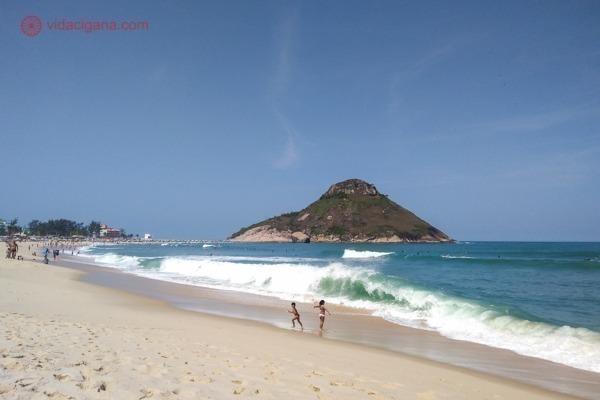 A Praia da Macumba com águas limpas e vista para a Pedra do Pontal. Perceba como a Praia do Pontal está cheia na esquerda da foto