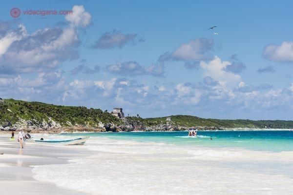 A Praia Paraíso com águas azul turquesa, areias brancas e as ruínas de Tulum ao fundo, acima das rochas cobertas de verde.