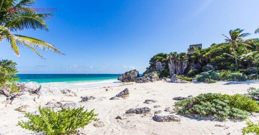 Onde ficar em Tulum: Uma praia paradisíaca de areias brancas com o mar do Caribe com as ruínas de Tulum do lado direito.